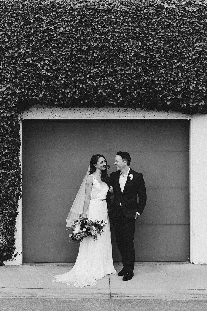 bride and groom pose in front of garage with large hedge darlington house la jolla wedding