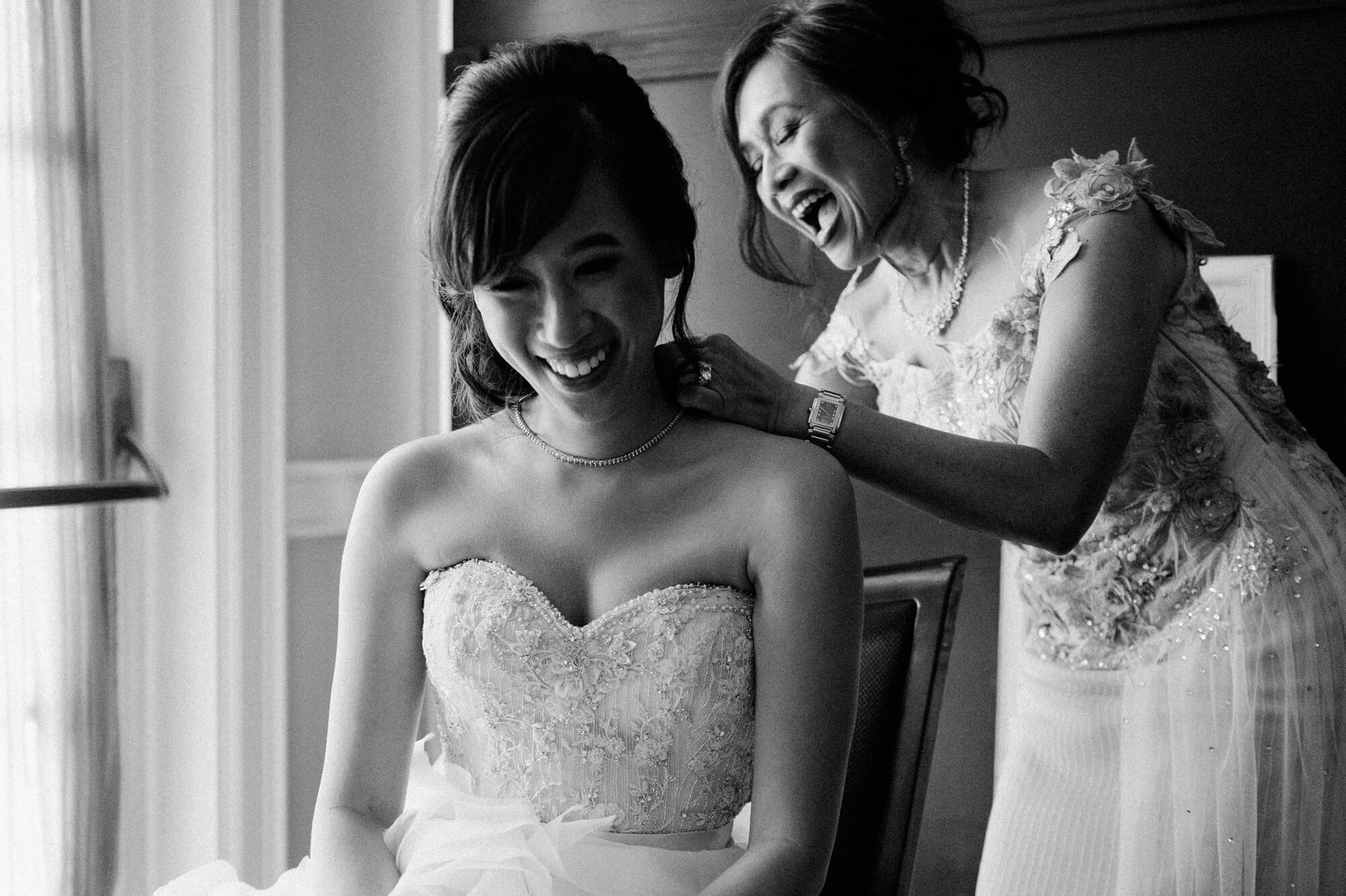 bride and mother laugh as mother helps with necklace