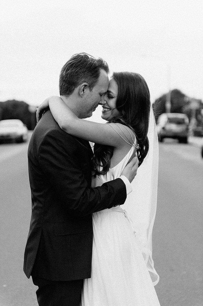 bride and groom embrace on marine street during their la jolla wedding at the darlington house