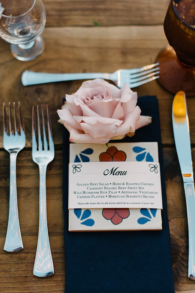printed menu and purple rose place setting on wooden table