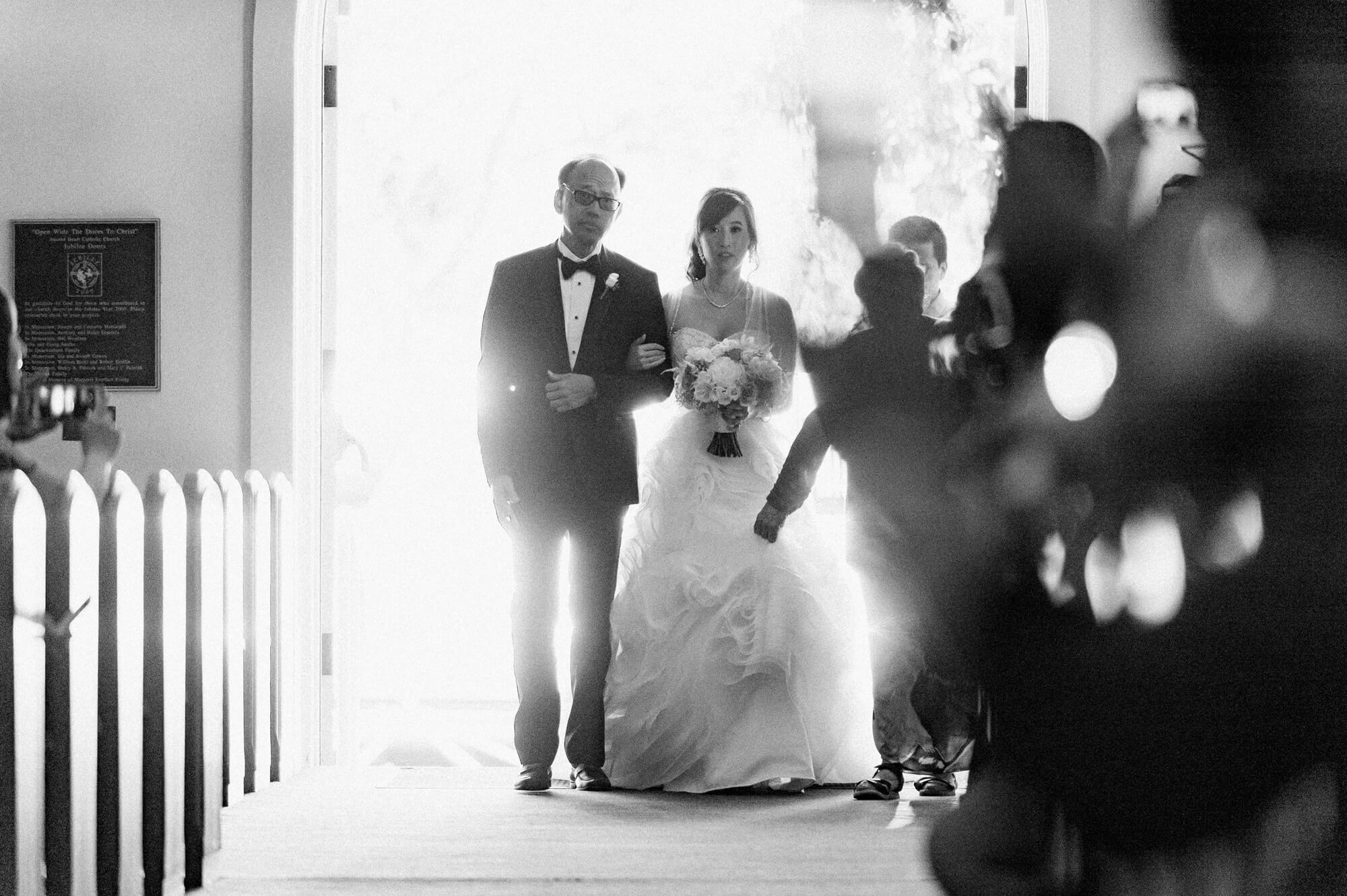 father and bride enter sacred heart church in coronado