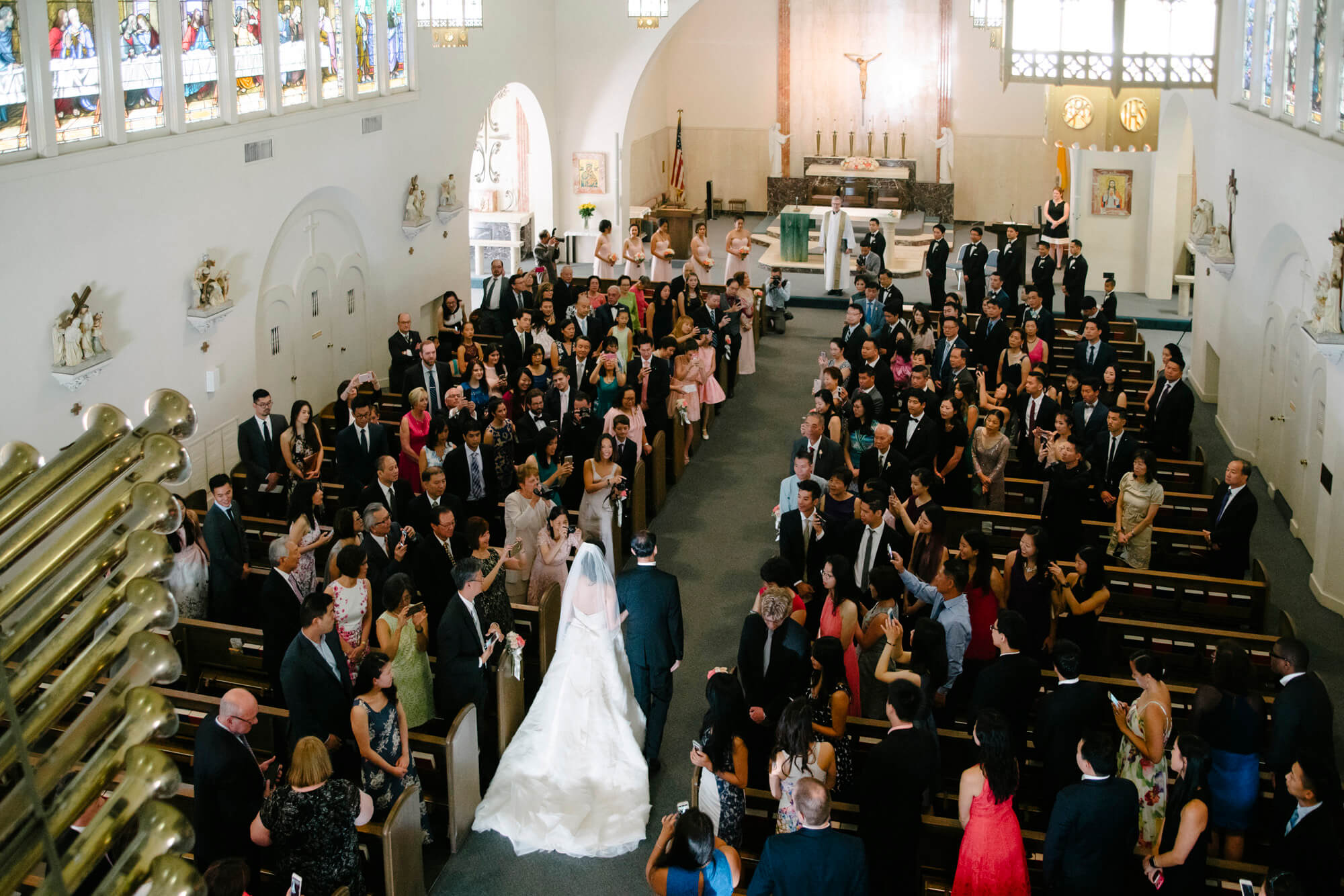 father and daughter walk down aisle seen from balcony sacred heart church coronado