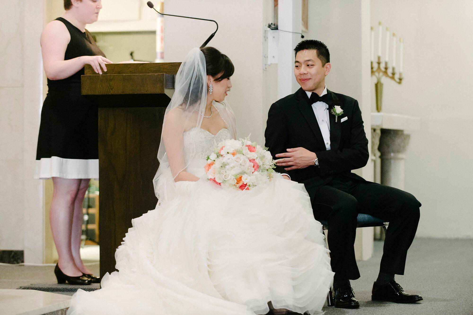bride and groom share smile sitting during catholic wedding ceremony