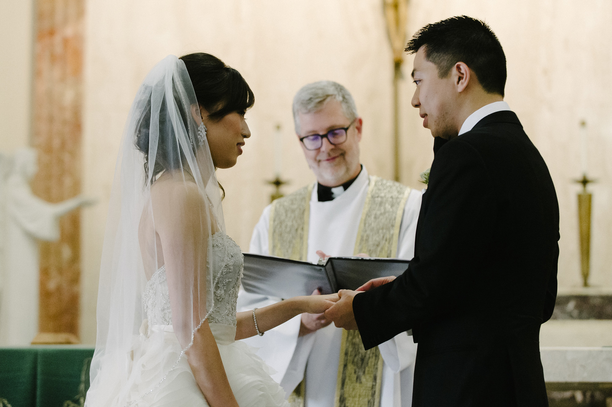 bride and groom exchange rings at during catholic wedding ceremony