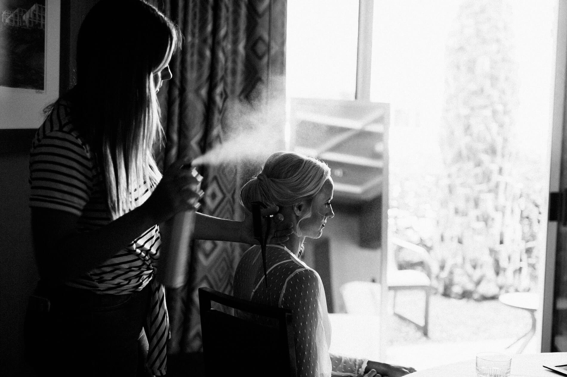 stylist spraying hairspray on bride