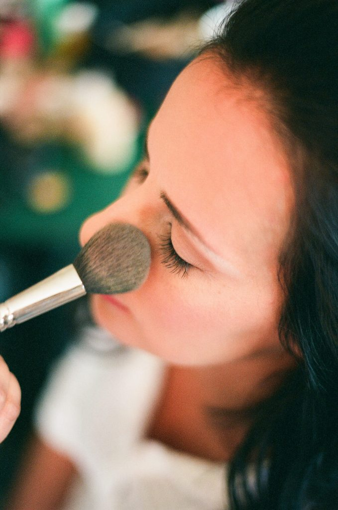 bride putting on makeup with brush