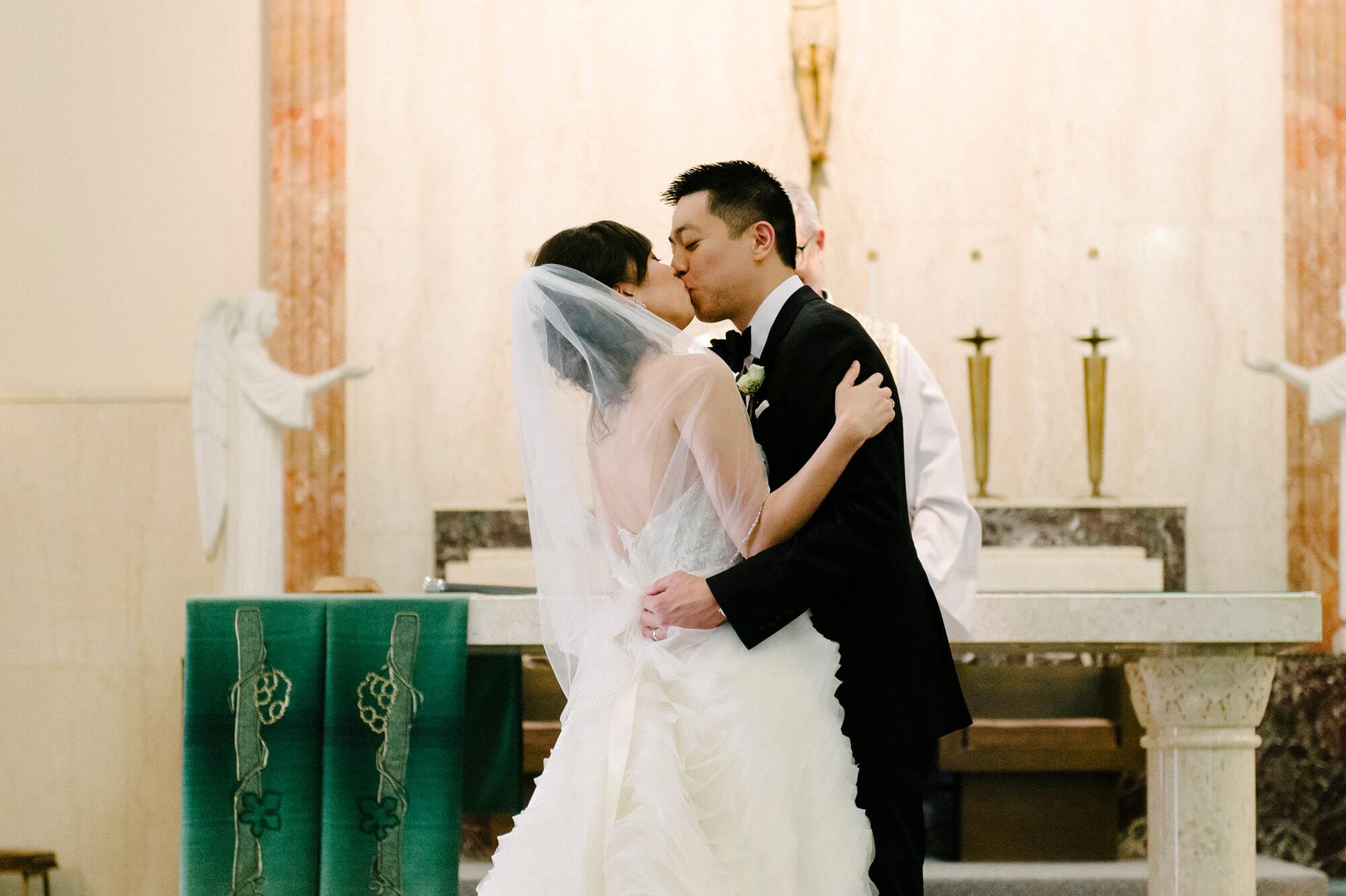 bride groom kiss catholic church wedding ceremony