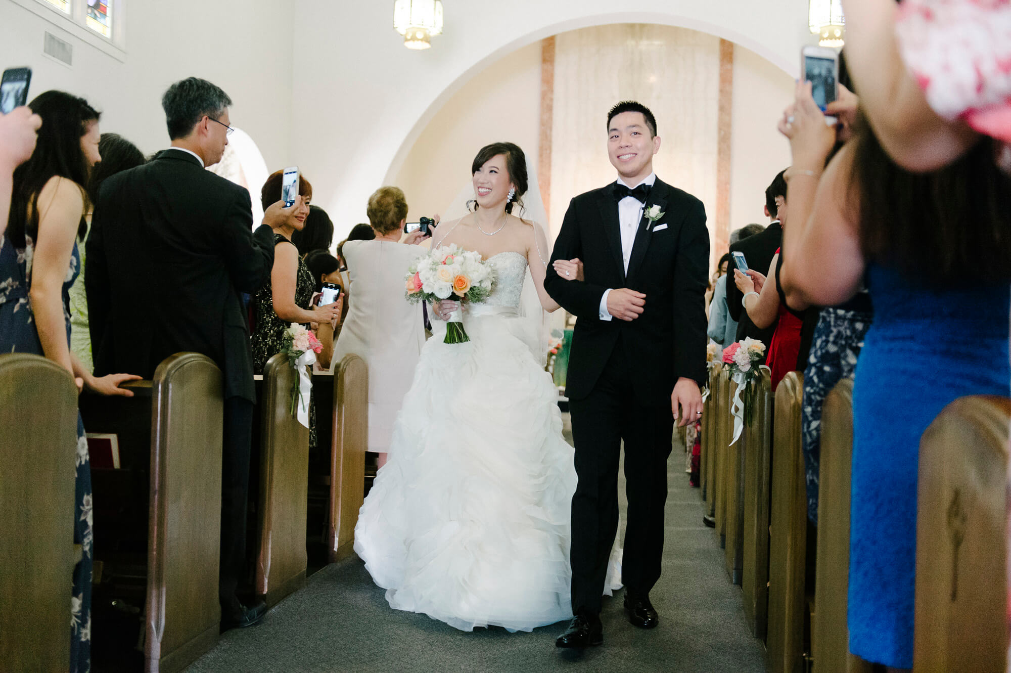 bride and groom recess down aisle after sacred heart coronado wedding ceremony