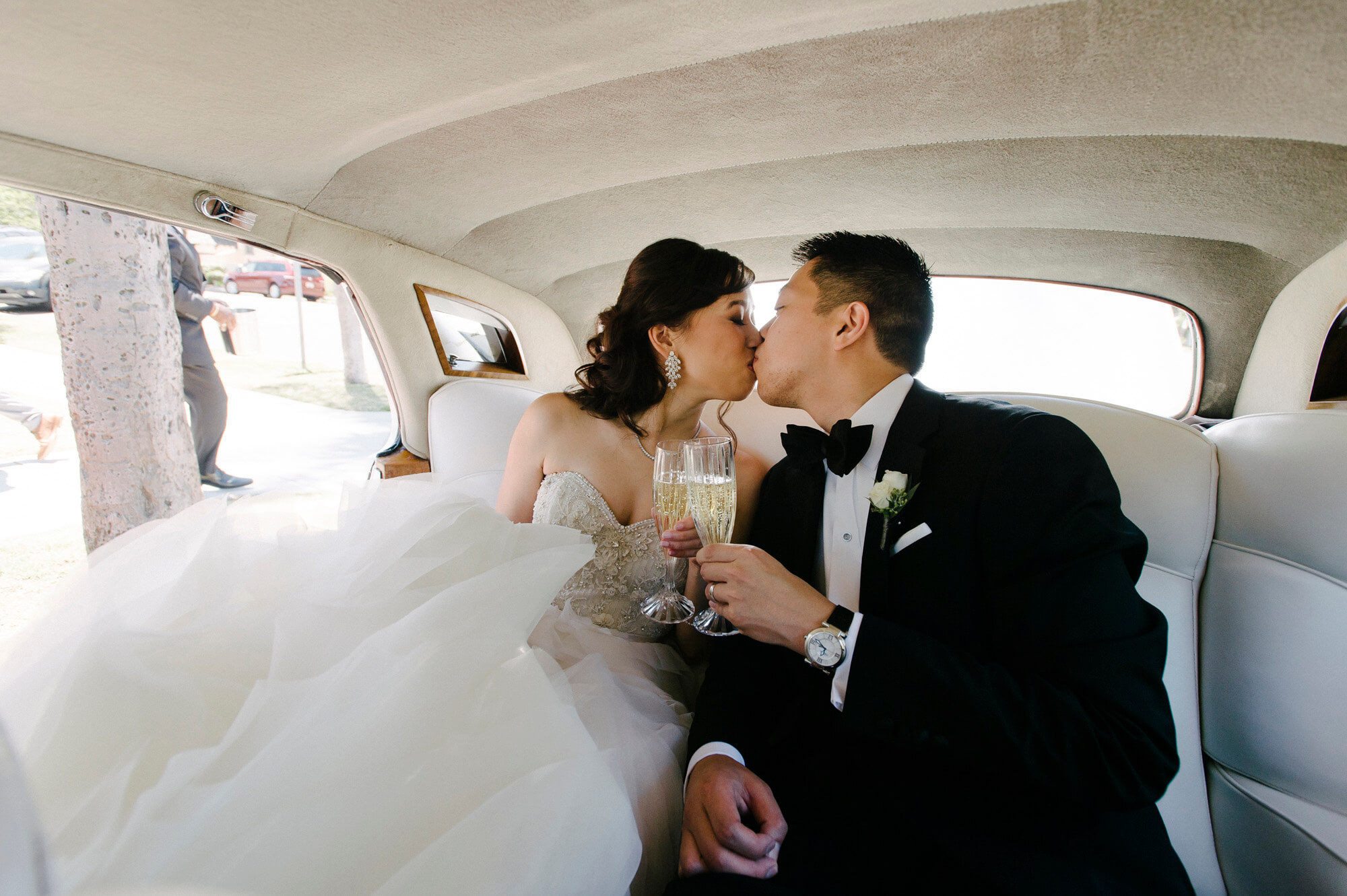 bride and groom toast champagne and kiss in vintage rolls royce limousine