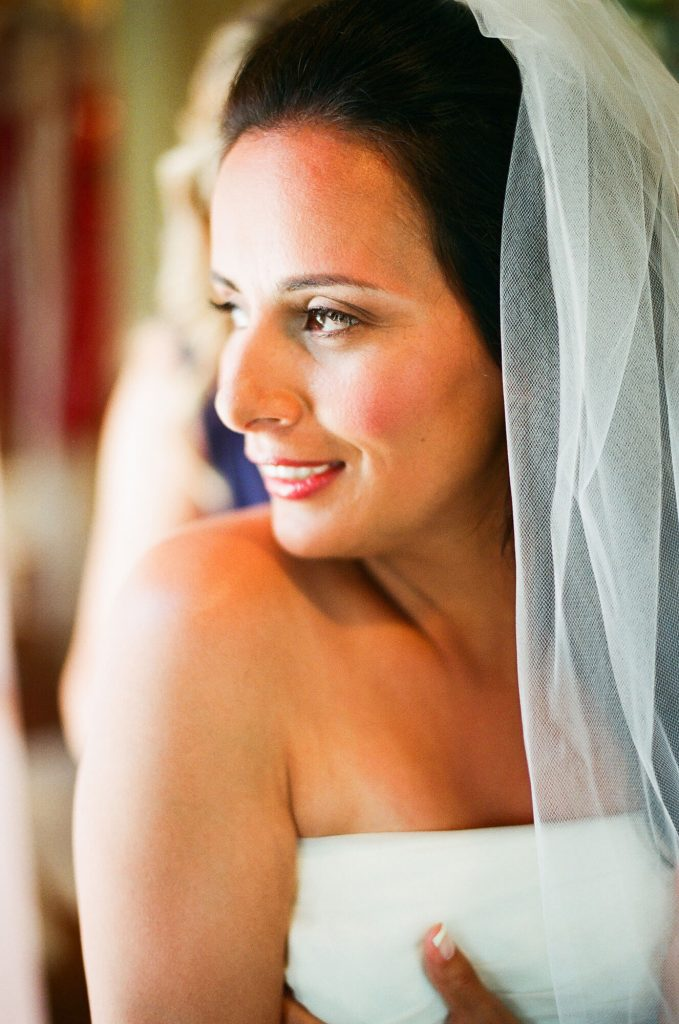 bride smiling while putting on wedding gown