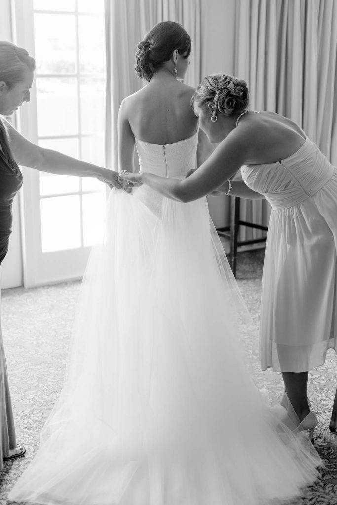 bridesmaid helping bride put on tule on gown