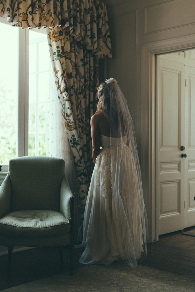 bride looks out window of bridal suite darlington house la jolla wedding
