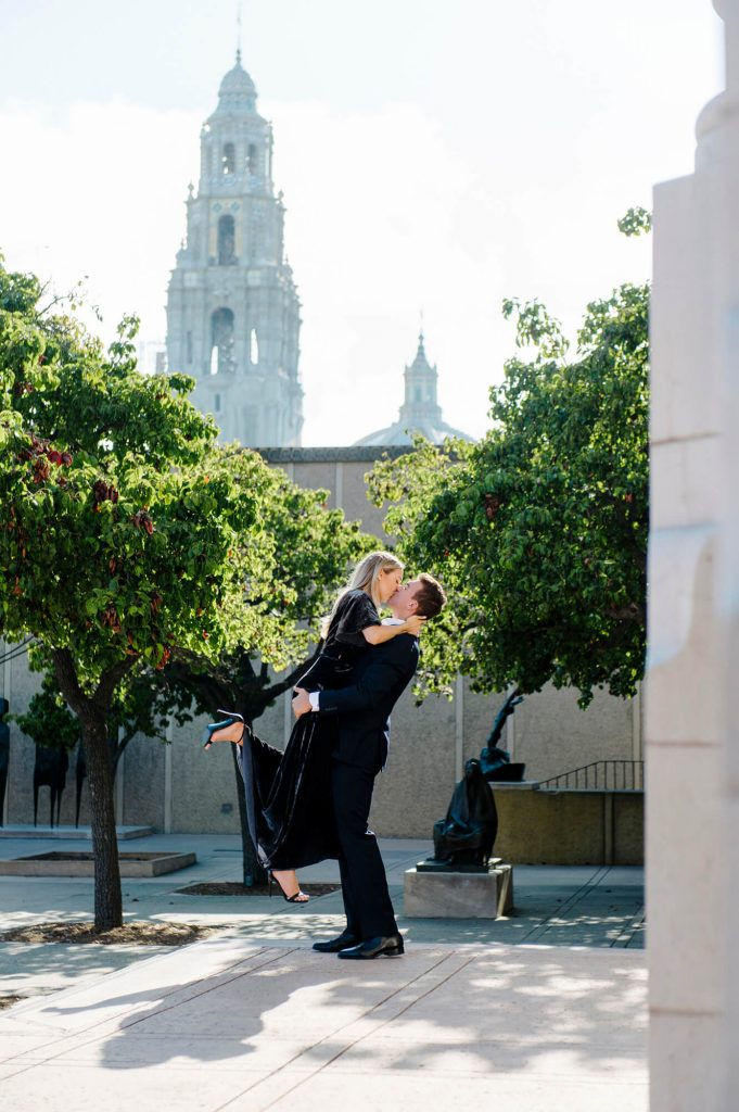 man lifts fiancee in air balboa park engagement
