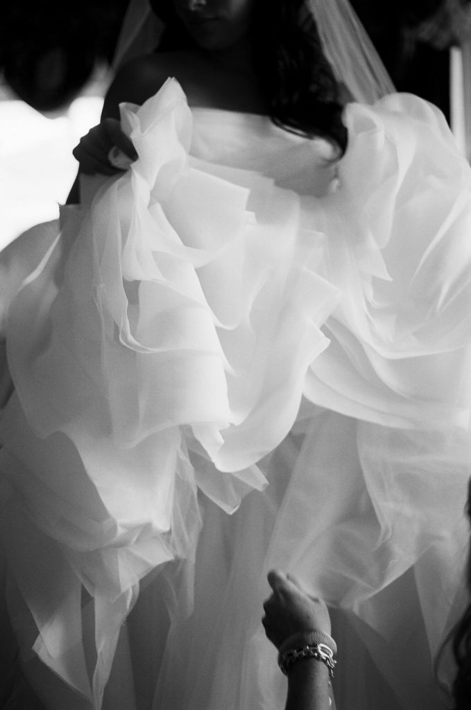 ruffles in dress being lifted by bride