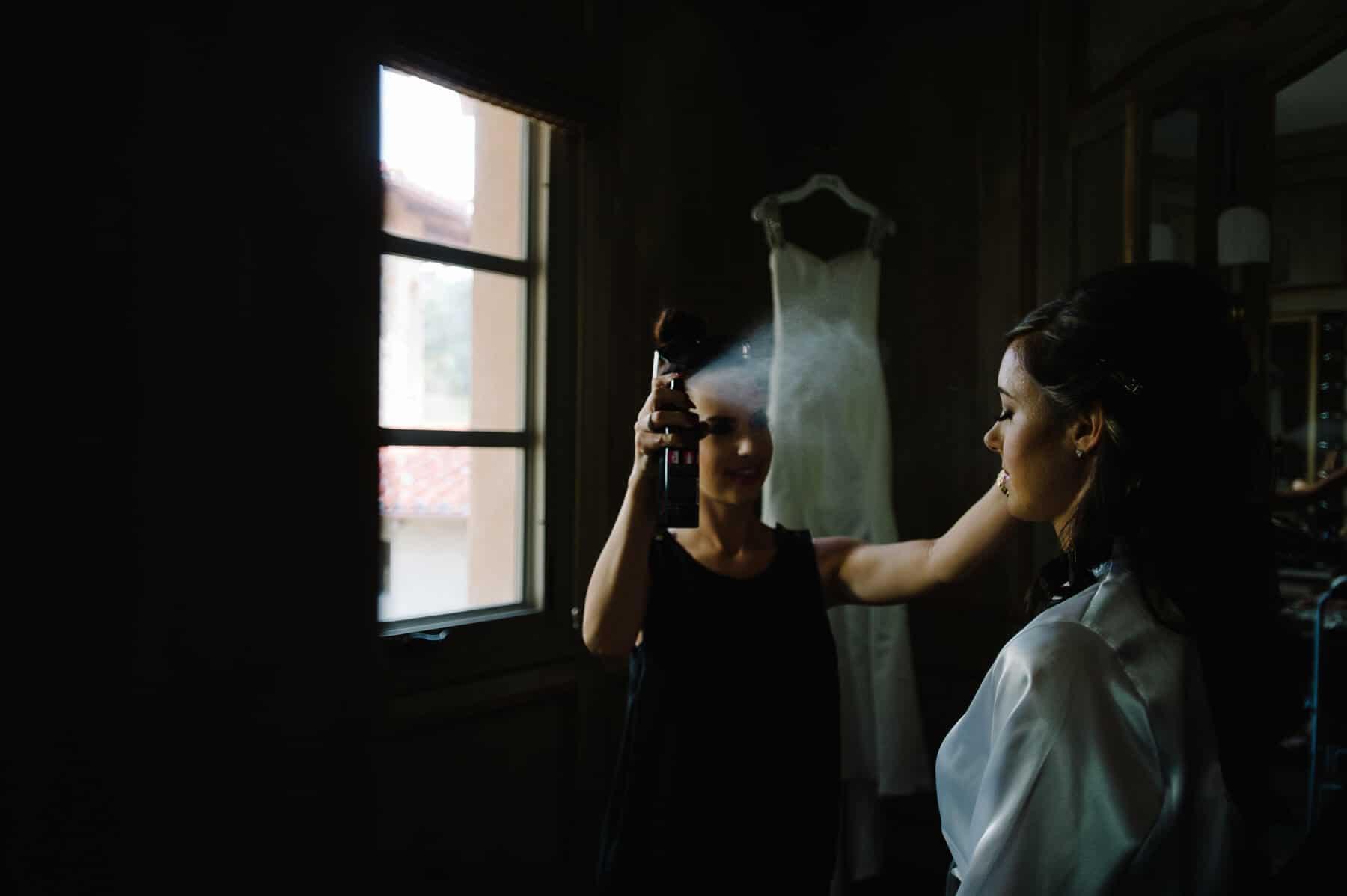 hair stylist spraying hairspray on bride's hair
