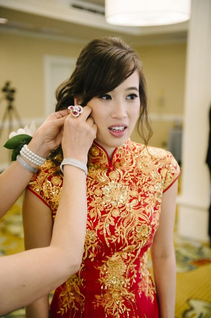 bride in traditional chinese dress puts on earrings before tea ceremony