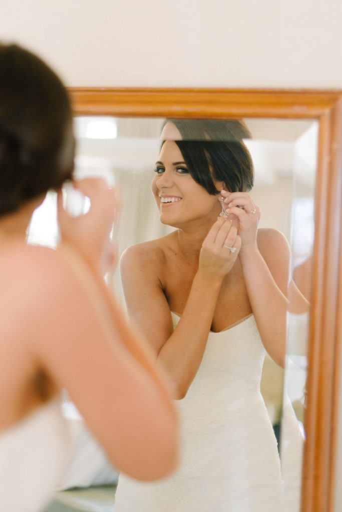 bride putting on earring in mirror lauberge hotel