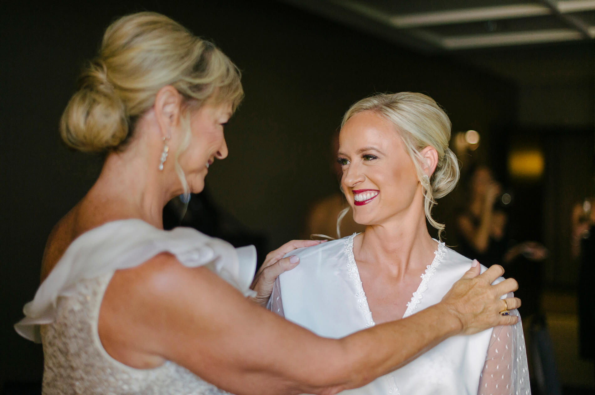 bride and mother sharing smiles before wedding