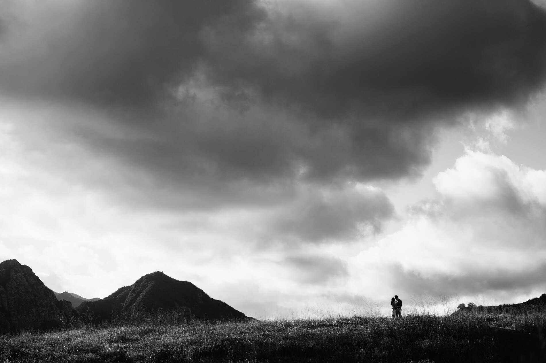 couple posing on ridge with dark clouds and peaks in background malibu creek state park engagement