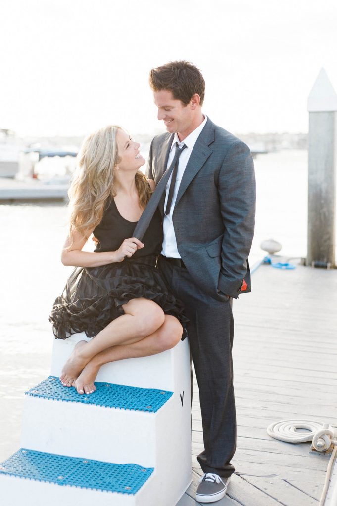 woman in black minidress pulls on tie of fiancee newport harbor yacht club engagement