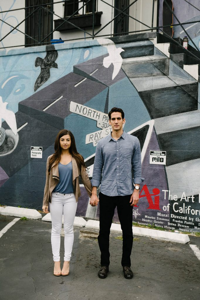 couple posing in front of public mural urban san diego engagement photo