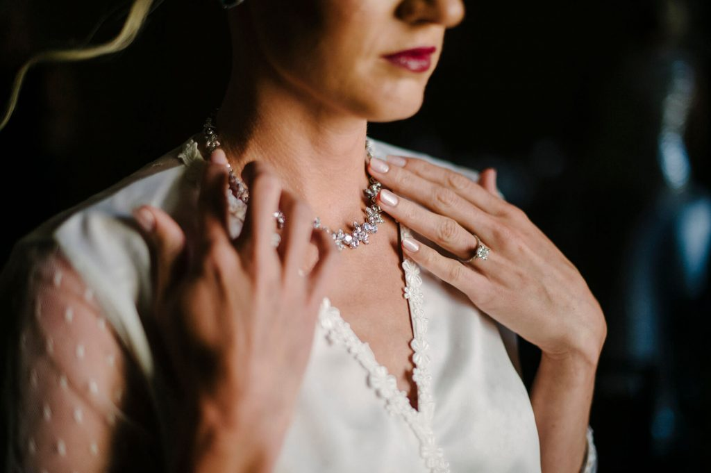 bride touching diamond necklace in bridal suite
