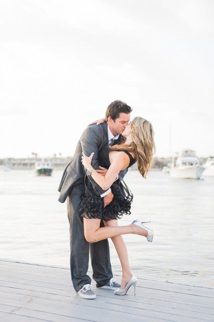 man kisses fiancee newport beach engagement photo