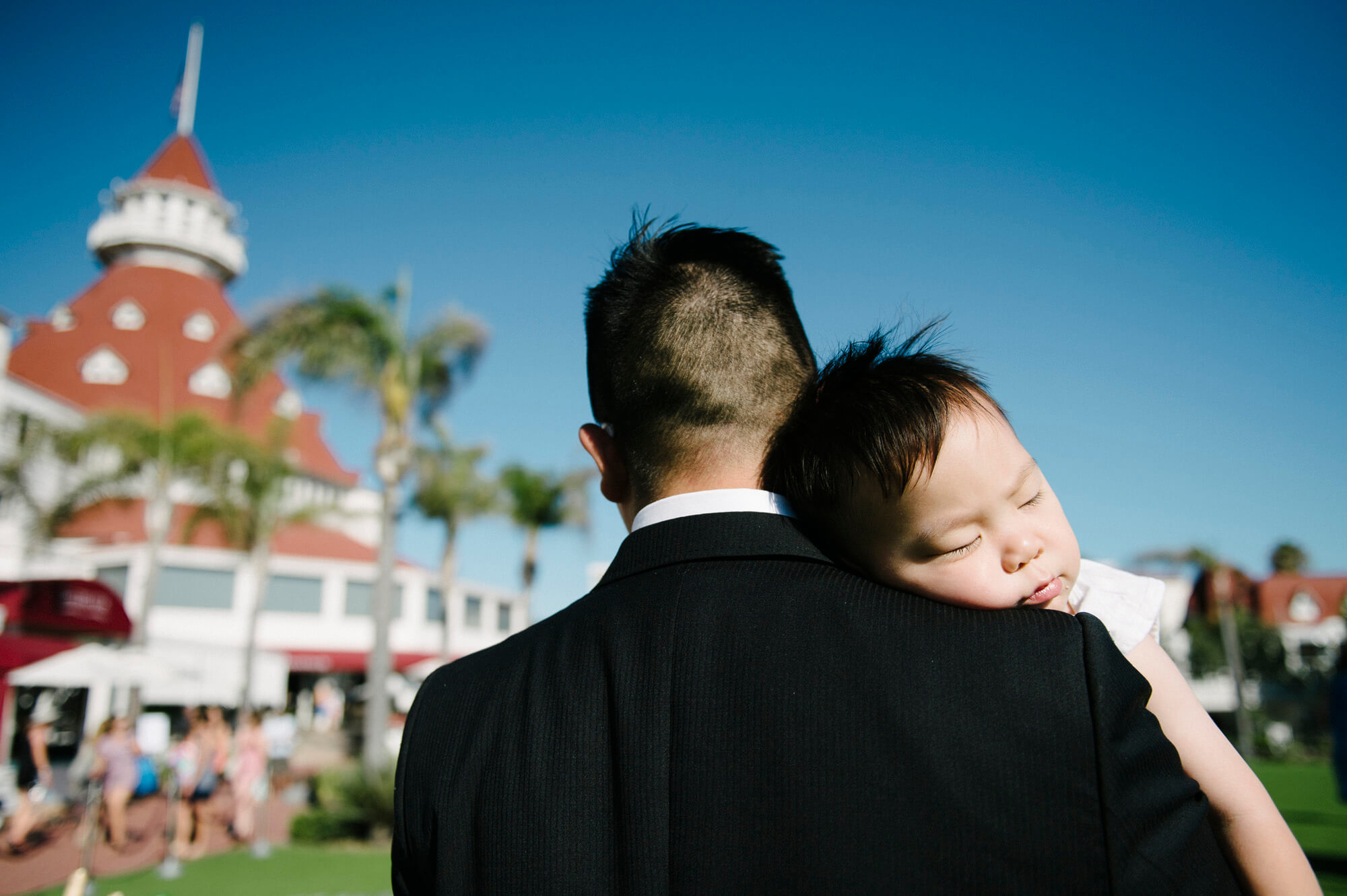 young child sleeps on dad's shoulder hotel del wedding reception