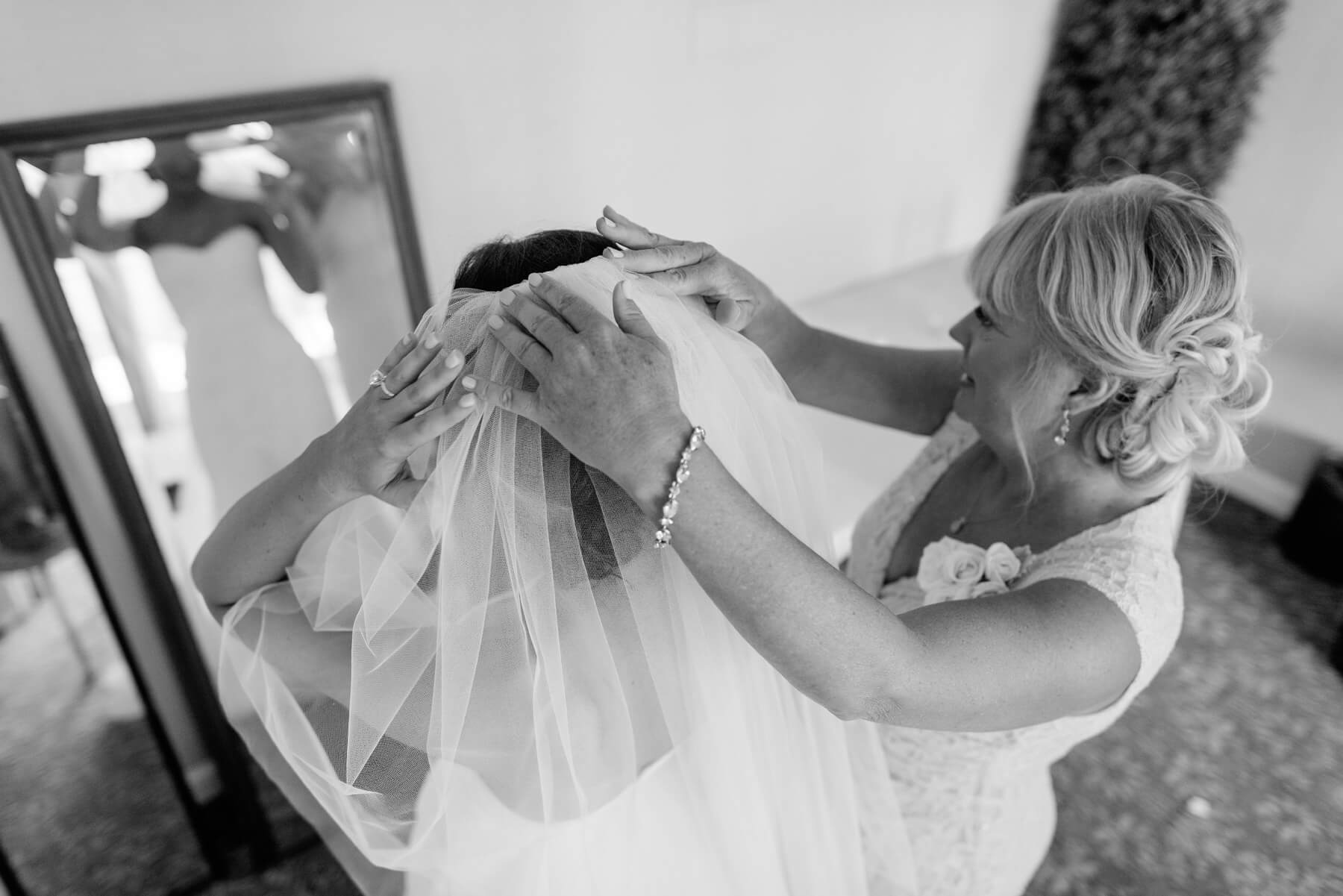 mother helps daughter bride with veil san diego beach wedding lauberge del mar