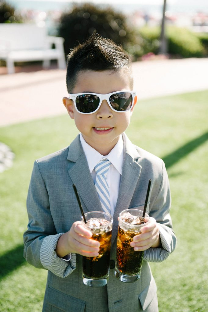 young wedding guest in gray suit with sunglasses holds two glasses of soda