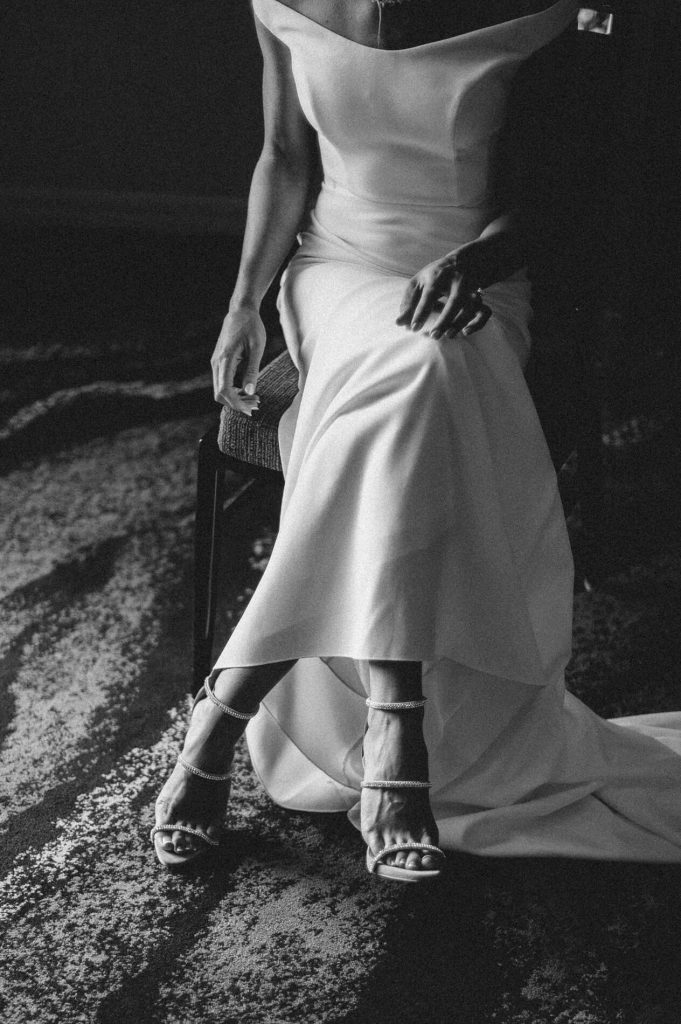 bride sitting with gown and shoes