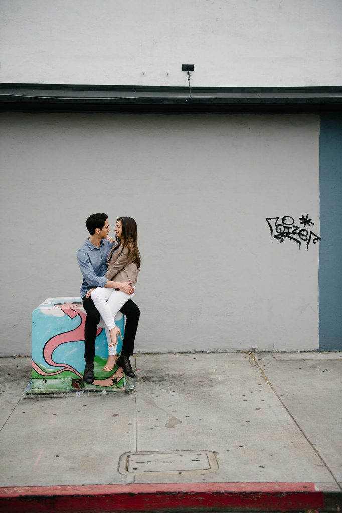 couple sitting on painted electrical box north park san diego