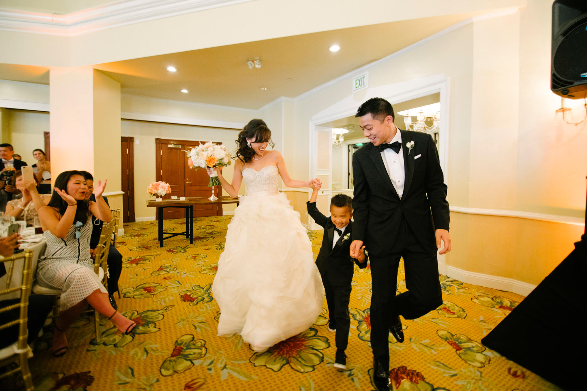bride and groom and young wedding guest make grand entrance