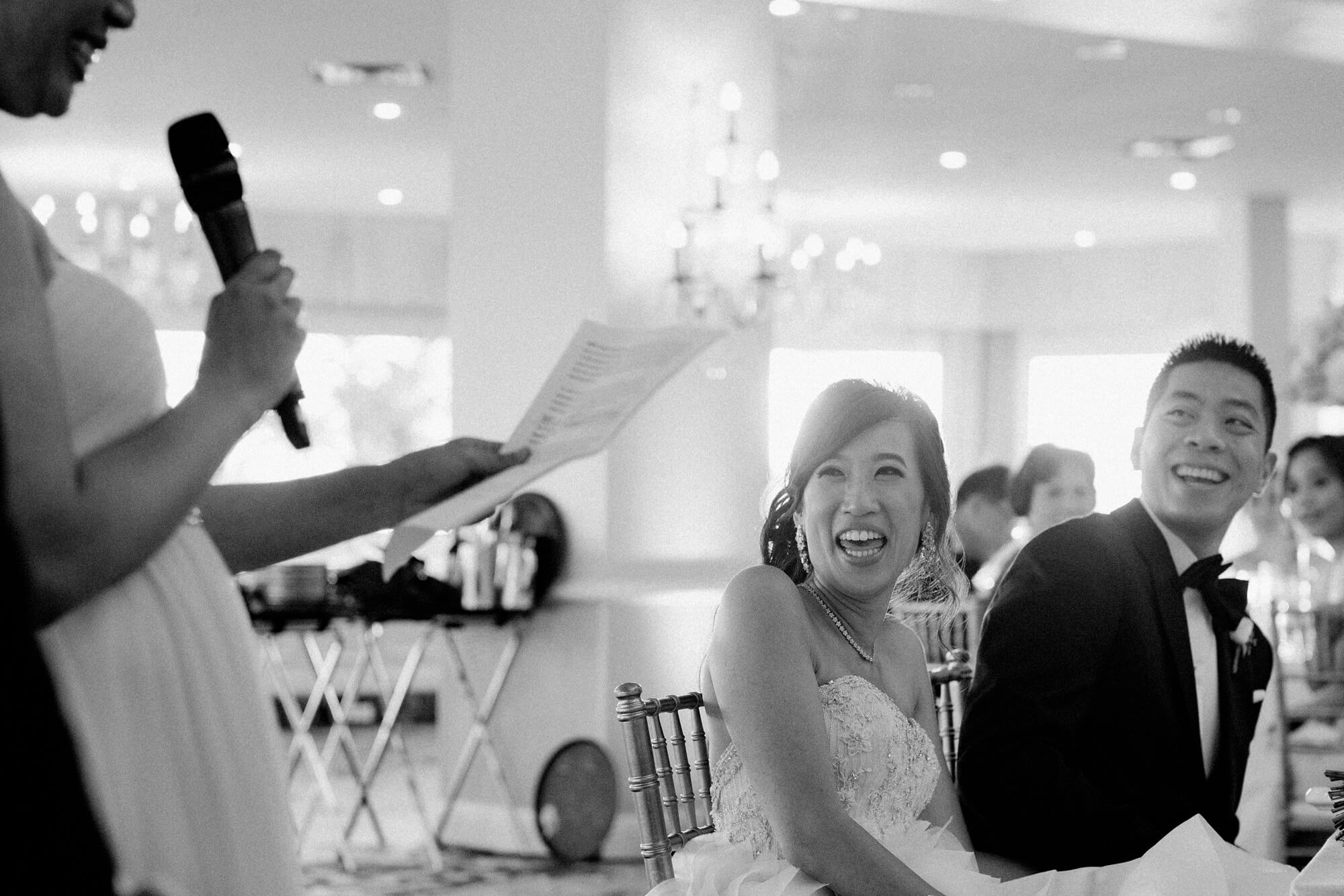 bride and groom laugh at maid of honor speech