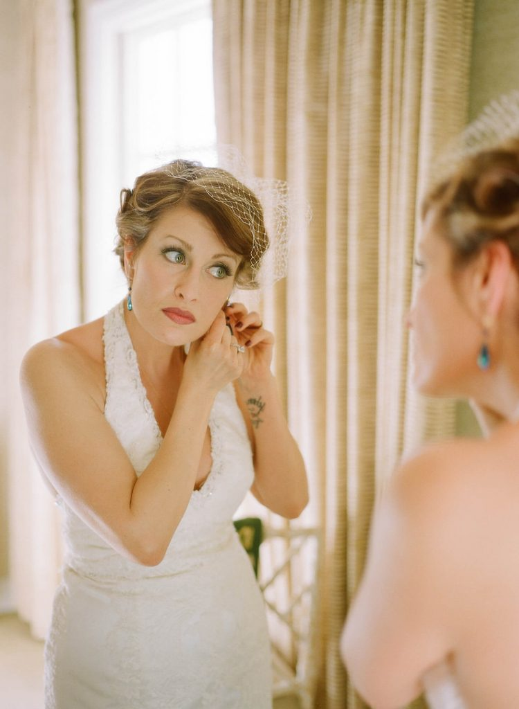 bride with vintage gown and birdcage veil puts on earrings