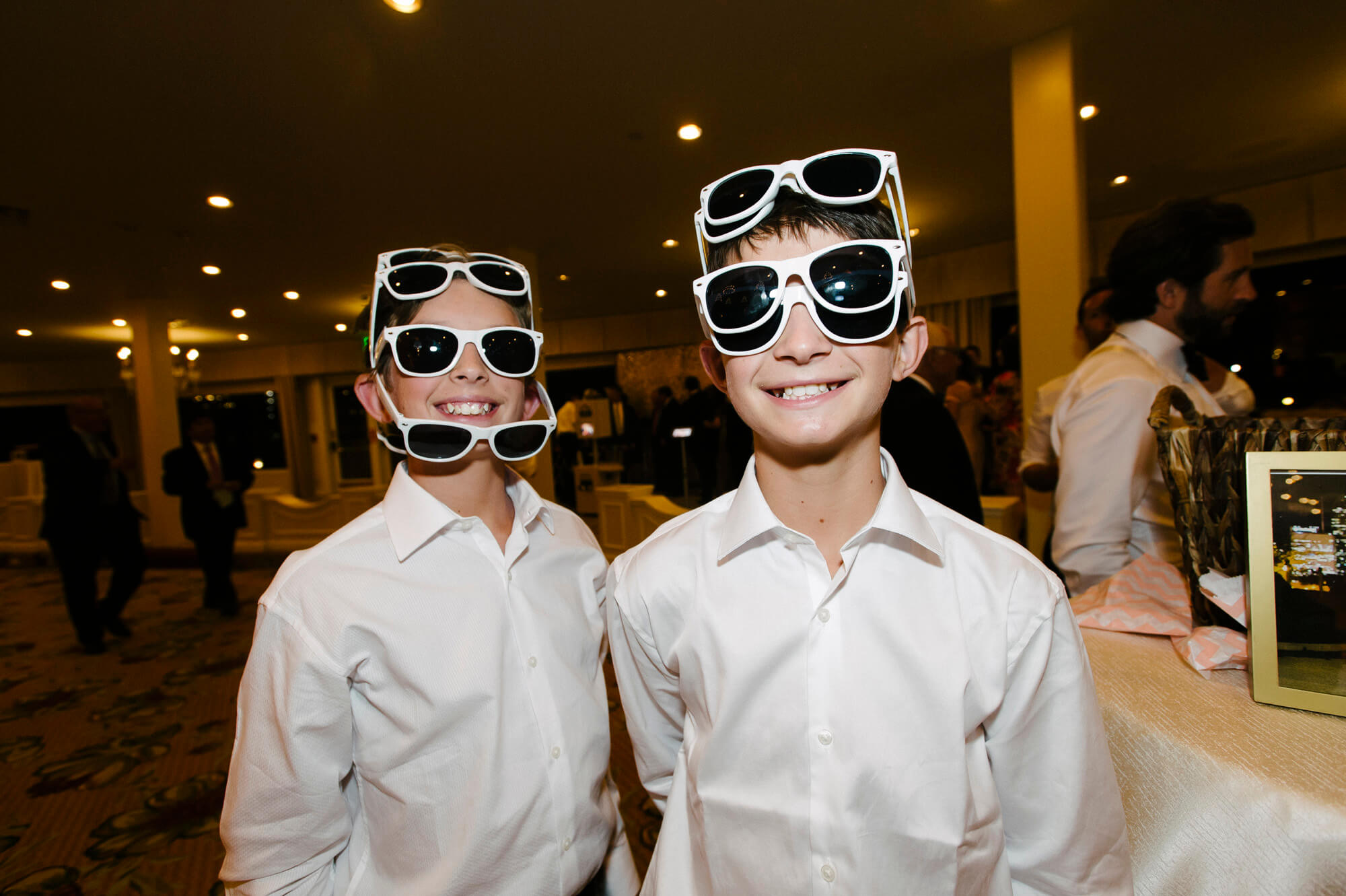 young wedding guests put on multiple pairs of sunglasses