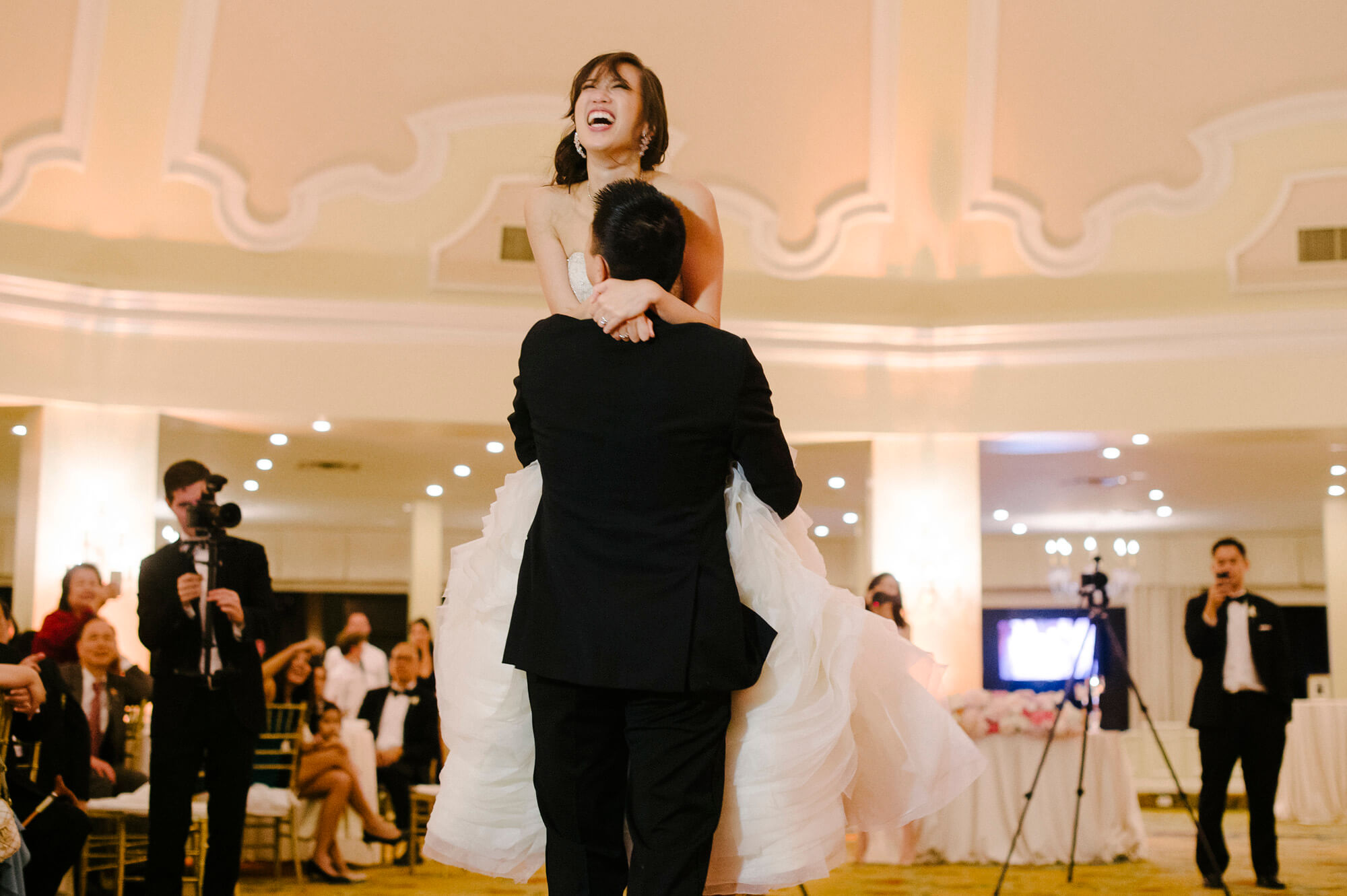 groom lifts bride in air first dance