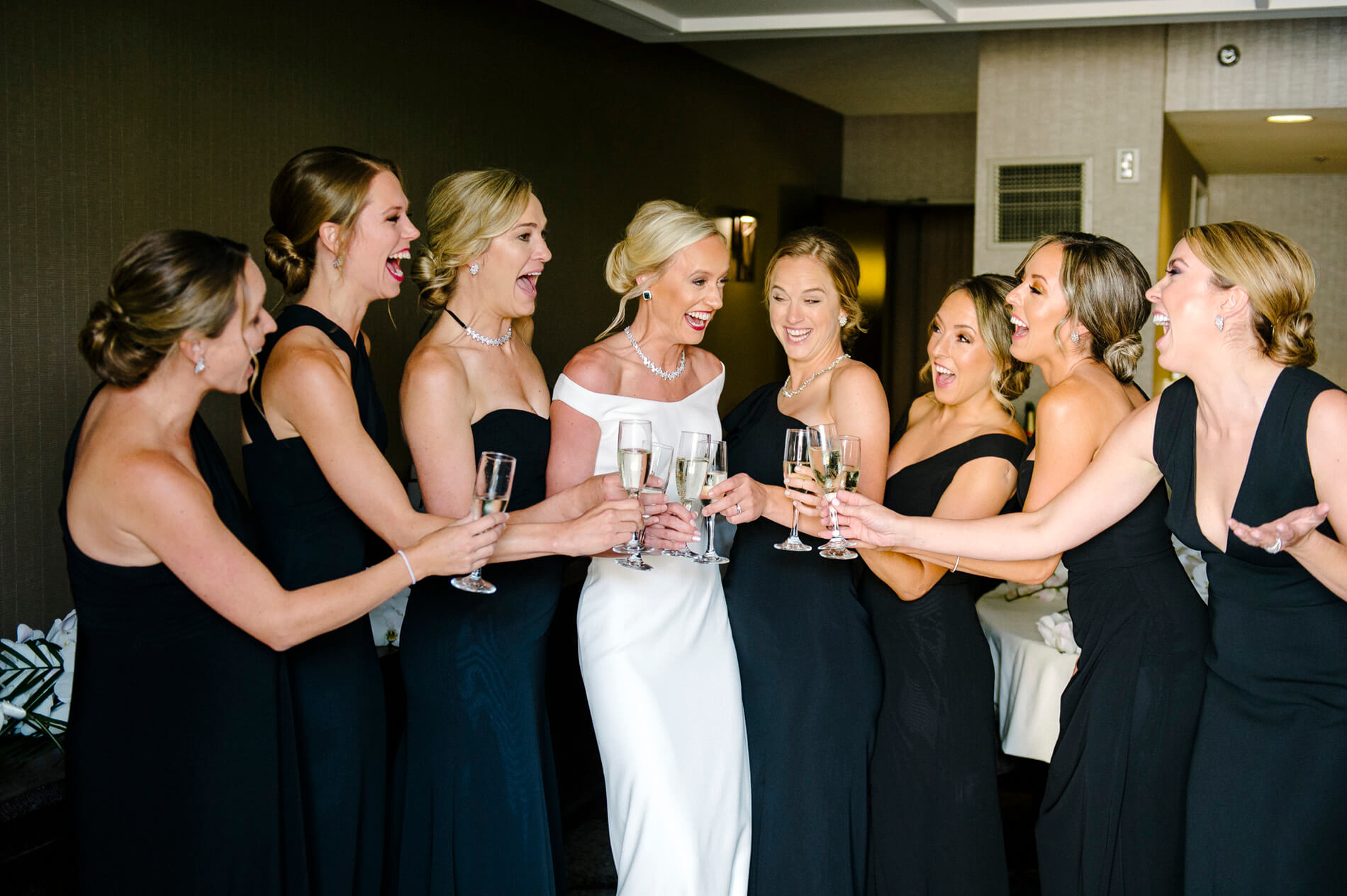 bride and bridesmaids saying cheers with champagne
