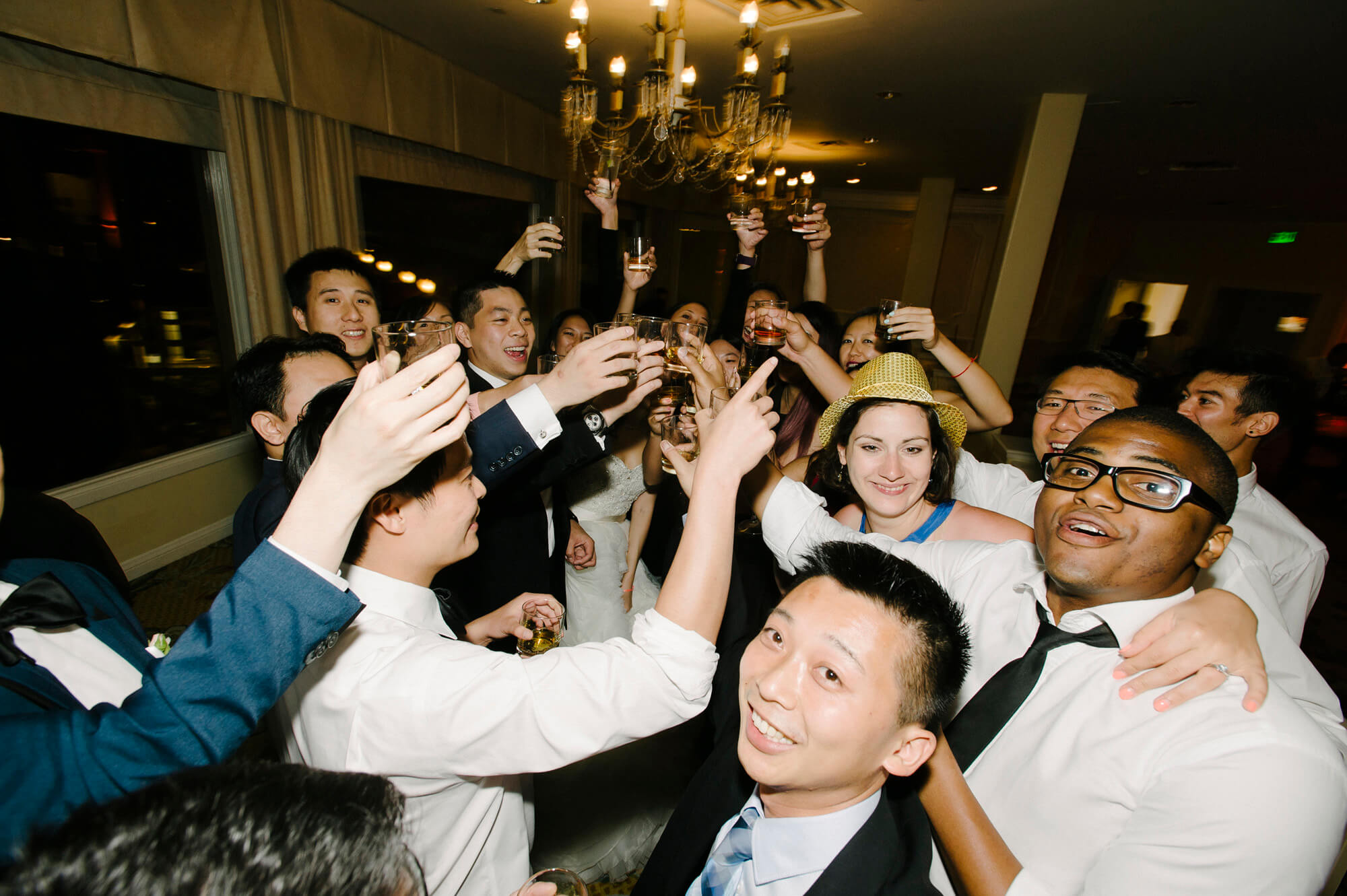 groom and wedding guests cheers tequila shots