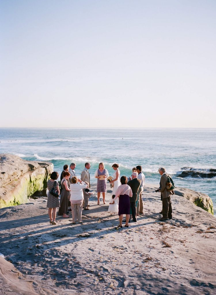 bride and groom and guests on rocks a windansea beach intimate wedding