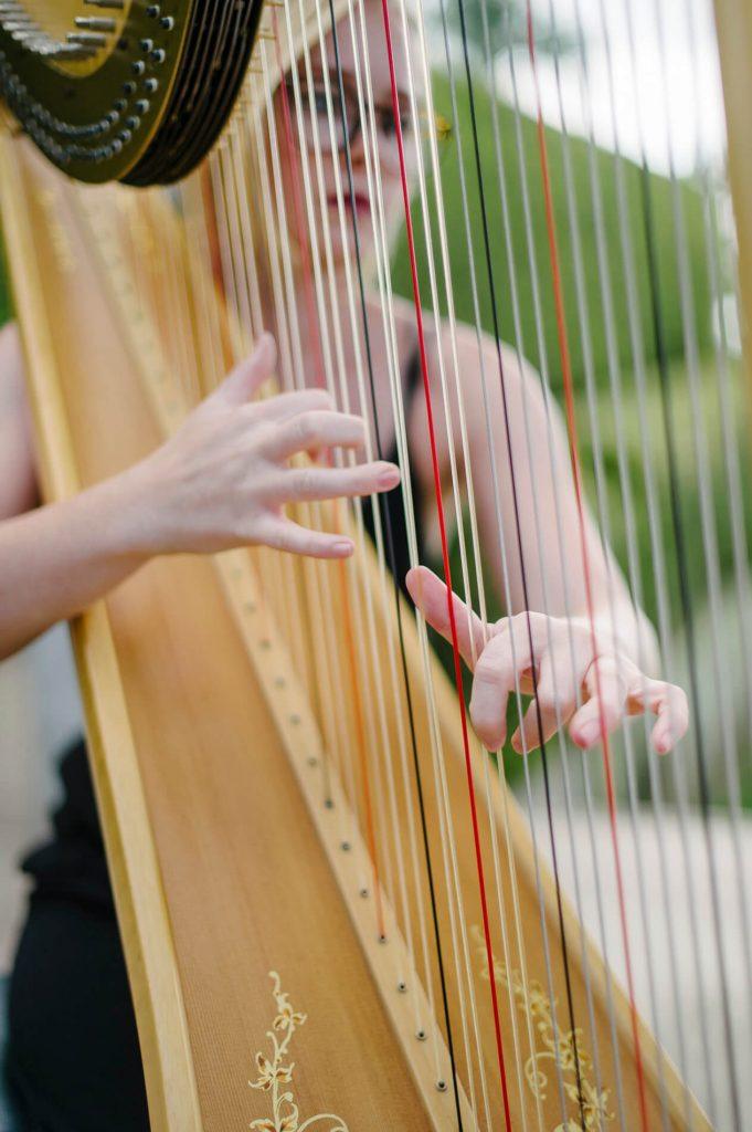 harpist plucking strings before wedding ceremony