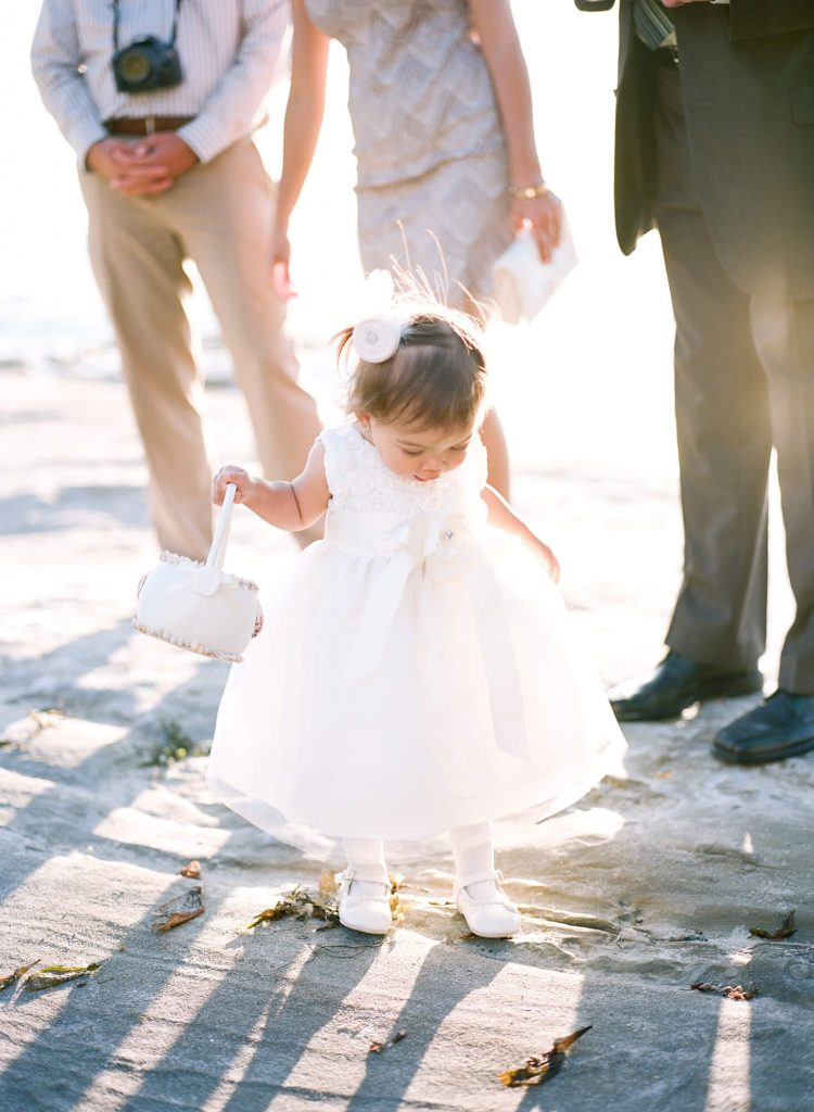 young flower girl on rocks during ceremony intimate windansea beach wedding