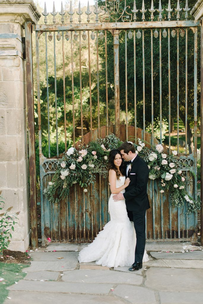 bride and groom embracing in front of french gates timeless san diego wedding