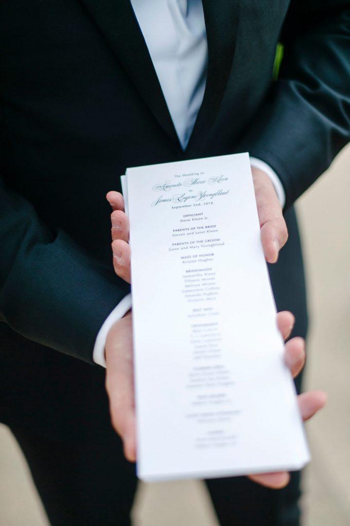 groomsman holding wedding ceremony programs