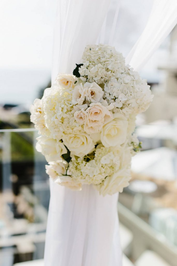 white flowers attached to wedding arch lauberge del mar