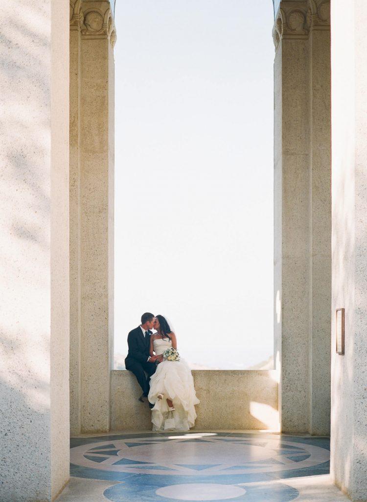 bride and groom sitting between large columns at wrigley memorial catalina island wedding