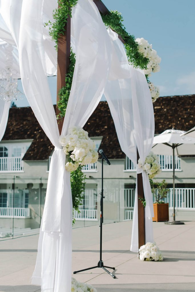 wooden wedding arch with flowers and tule pacific terrace lauberge del mar