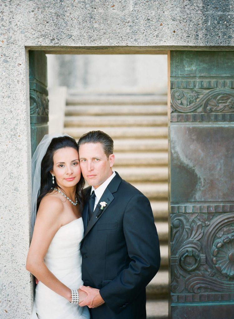 bride and groom posing near steel door at wrigley memorial catalina island wedding