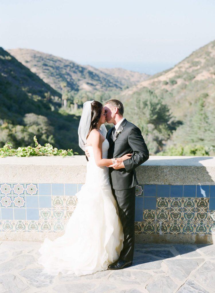 bride and groom kissing near wall at wrigley memorial catalina island