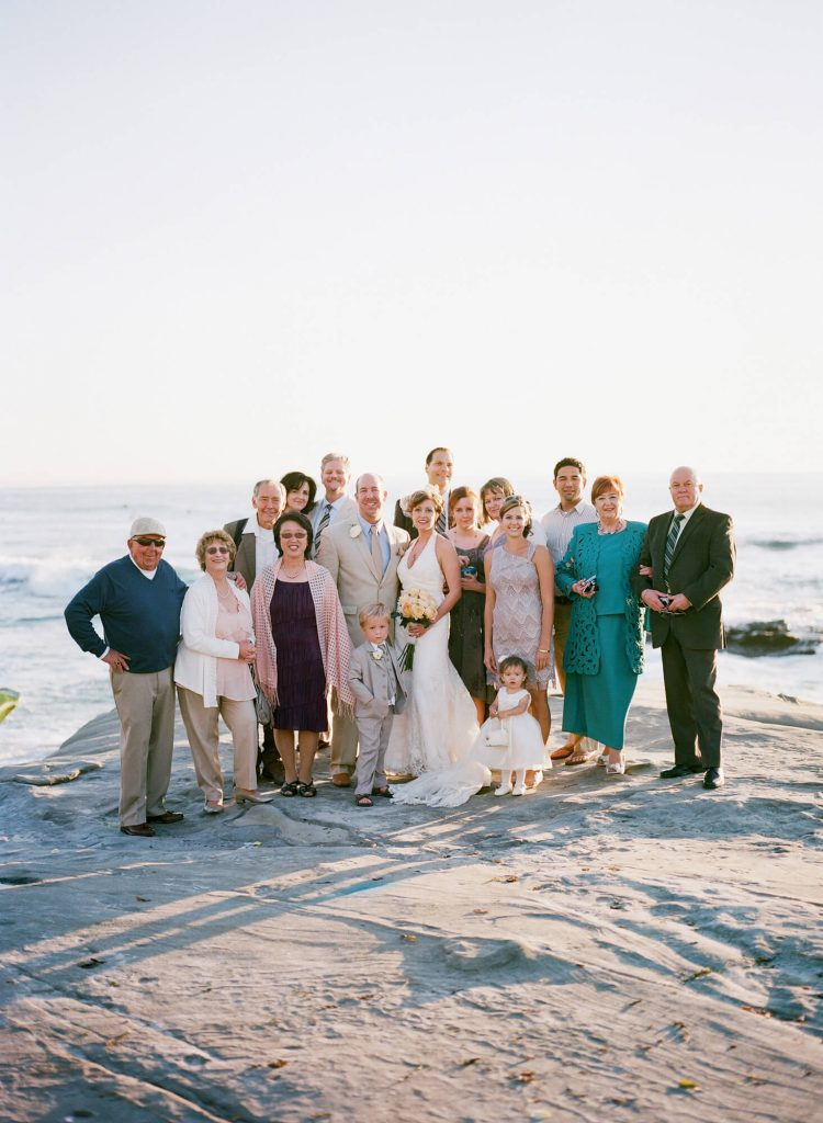 bride and groom and guests pose group photo windansea beach wedding